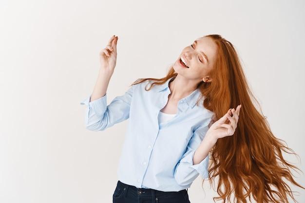 긴 빨간 머리를 가진 아름다운 여성이 손가락을 튕기고 춤을 추며 음악을 들으며 흰 벽에 기대어 서 있습니다.