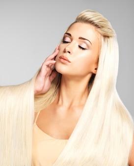 Красивая женщина с длинными прямыми светлыми волосами. фотомодель позирует