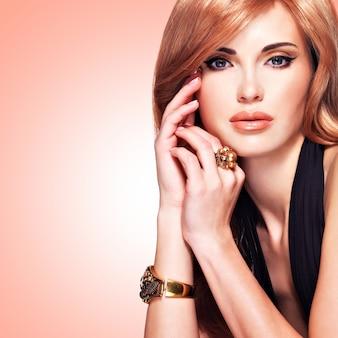 Bella donna con capelli rossi lunghi dritti in un vestito nero che tocca il suo fronte. modello di moda in posa.