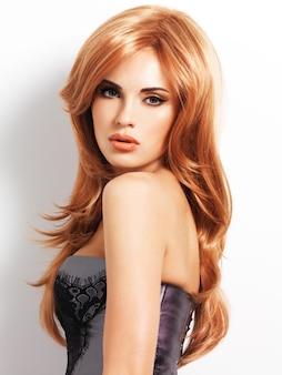 긴 직선 붉은 머리를 가진 아름 다운 여자입니다. 흰 벽에 패션 모델