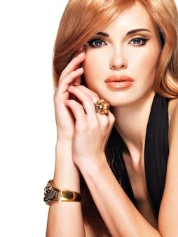 그녀의 얼굴을 만지고 검은 드레스에 긴 직선 붉은 머리를 가진 아름 다운 여자. 패션 모델 포즈. 흰색 절연