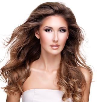 長いウェーブのかかった髪のポーズの美しい女性。白で隔離