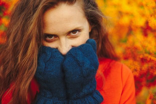 Bella donna con lunghi capelli ondulati toccando il mento con lana morbida
