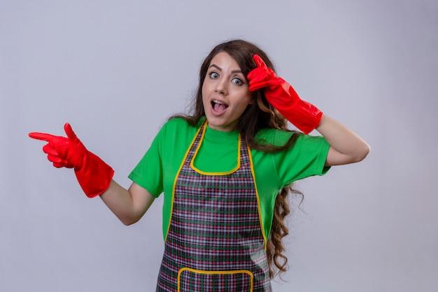 エプロンとゴム手袋を着用して長いウェーブのかかった髪の美しい女性が立っている側に指で驚いてショックを受けて指さして