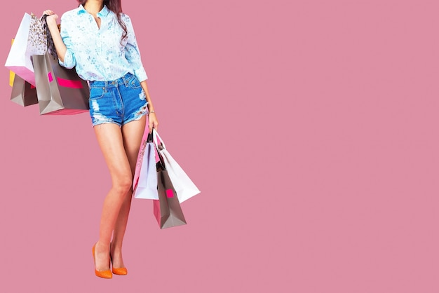 Beautiful woman with a lot of shopping bags on a pink background