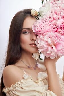 ピンクの花をたくさん手にした美しい女性。長い髪のセクシーな女性