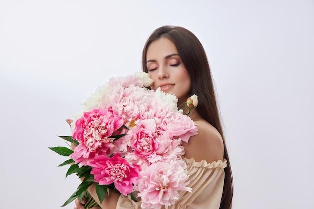 Красивая женщина с множеством розовых цветов в руках.