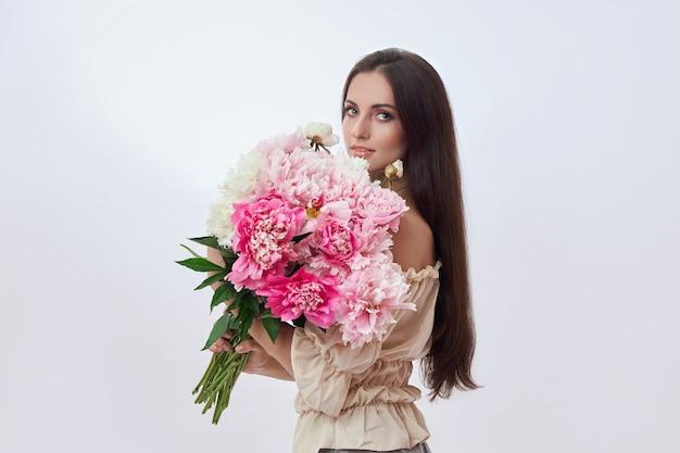 彼女の手にピンクの花がたくさんある美しい女性。