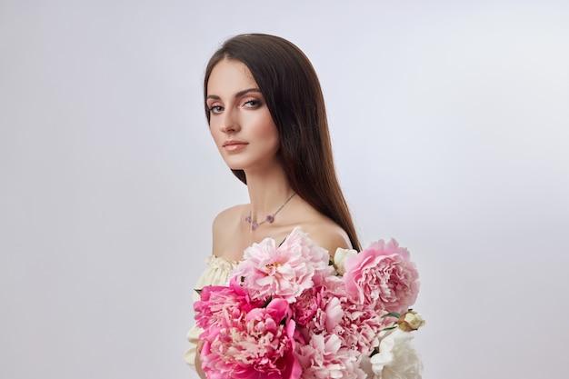 彼女の手にピンクの花がたくさんある美しい女性