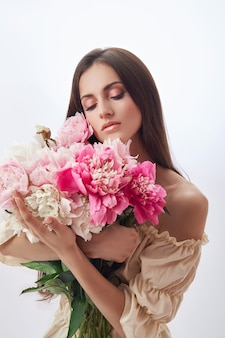 Beautiful woman with lots of pink flowers in her hands
