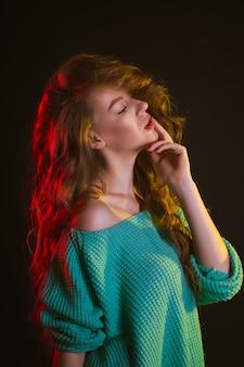 スタジオで暗闇の中で青々とした髪の美しい女性
