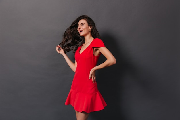 暗い背景に赤い服でポーズをとる壮大なウェーブのかかった髪の美しい女性。