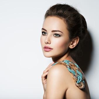 メイクアップネックレスと美容ファッション写真を持つ美しい女性
