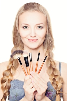 Beautiful woman with makeup brushes. make-up concept