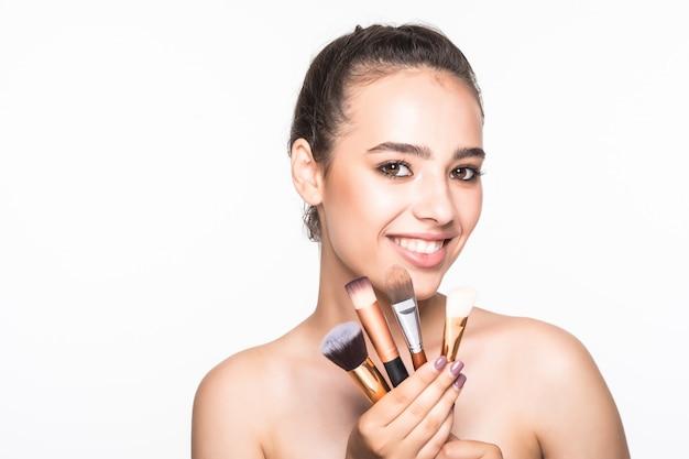 Bella donna con le spazzole di trucco vicino al suo fronte isolato sulla parete bianca