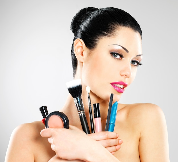 彼女の顔の近くに化粧ブラシを持つ美しい女性。かわいい女の子が化粧ツールでスタジオでポーズをとる