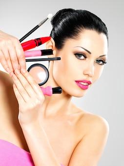 Bella donna con strumenti cosmetici trucco vicino al suo viso.