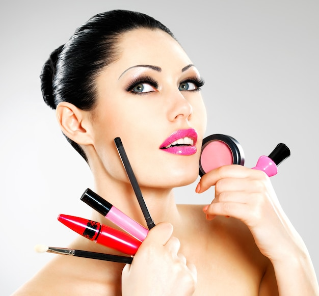 Beautiful woman with makeup cosmetic tools near her face.