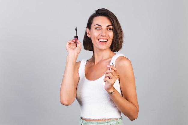 Красивая женщина с макияжем держит черную кисть для туши на серой стене, концепция красоты