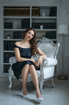 A beautiful woman with makeup and red lipstick is sitting in a black dress on a white chair