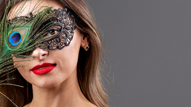 Beautiful woman with mask and peacock feather