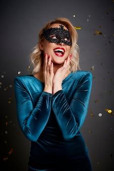 Красивая женщина с маскарадной маской, глядя на копию пространства