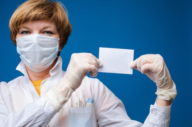 의료 마스크와 아름 다운 여자는 종이의 작은 흰색 시트를 보유