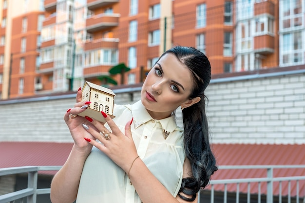 Beautiful woman with model of house on construction site