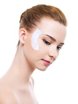 얼굴에 로션 화장품 크림을 가진 아름 다운 여자-흰색