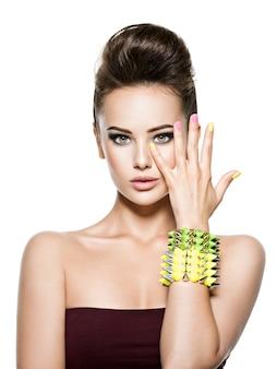Красивая женщина с разноцветными ногтями и браслетом с шипами на руке