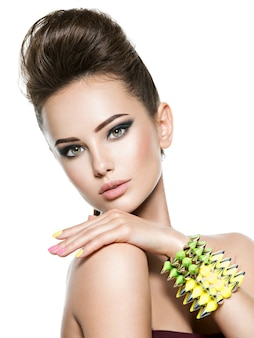 Beautiful  woman with multicolored nails and studded bracelet on hand