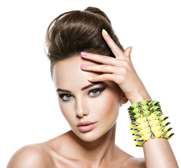Bella donna con unghie multicolori e bracciale borchiato a portata di mano