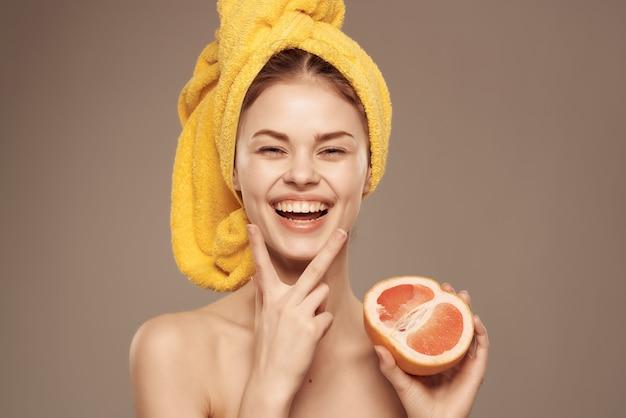 샤워 자몽을 손으로 자른 후 벗은 몸을 가진 아름다운 여성