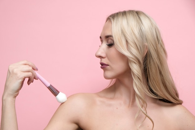 Beautiful woman with naked shoulders holding brush on pastel pink background