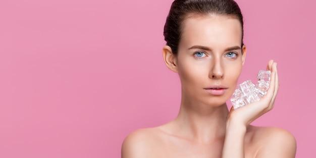 顔の近くに角氷を保持している自然な化粧の美しい女性
