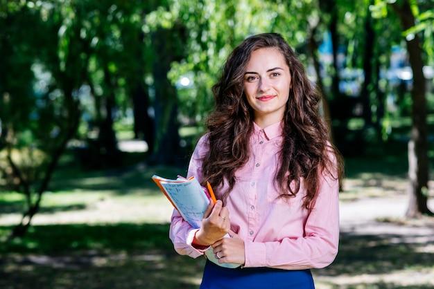 公園でノートブックを持つ美しい女性