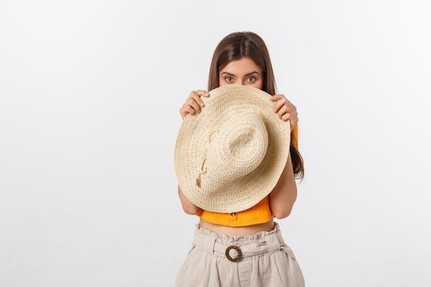 彼女の帽子の後ろに隠れているオレンジ色のブラウスと美しい女性
