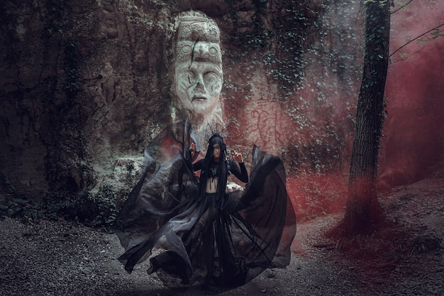 A beautiful woman with pale skin in a black dress and in the black crown. gothic look. outfit for halloween. a woman with colored smoke against the sculpture of an idol