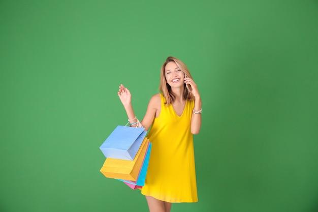 緑の上の紙袋を持つ美しい女性