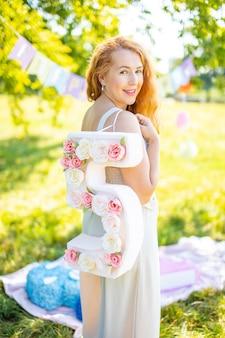 Красивая женщина с бумажным номером с цветами в ручных украшениях, сделанных своими руками небольшой б ...