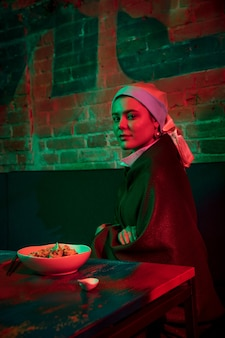 Beautiful woman with a pearl earring taking lunch in modern cafe