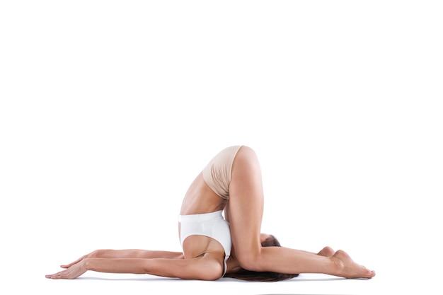 Красивая женщина с совершенным телом практикуя йога представляет полную длину в студии изолированной на белой предпосылке. концепция здорового образа жизни.