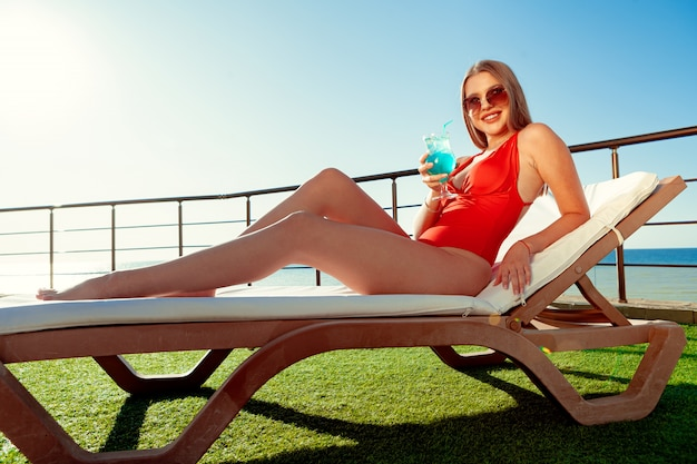 Beautiful woman with perfect body sunbathing on sunbed