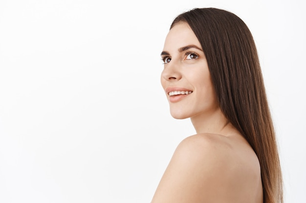 Beautiful woman with perfect clean, hydrated shiny face and long natural hair, brunette female model looking aside at copy space logo of skincare haircare cosmetics, standing naked shoulders