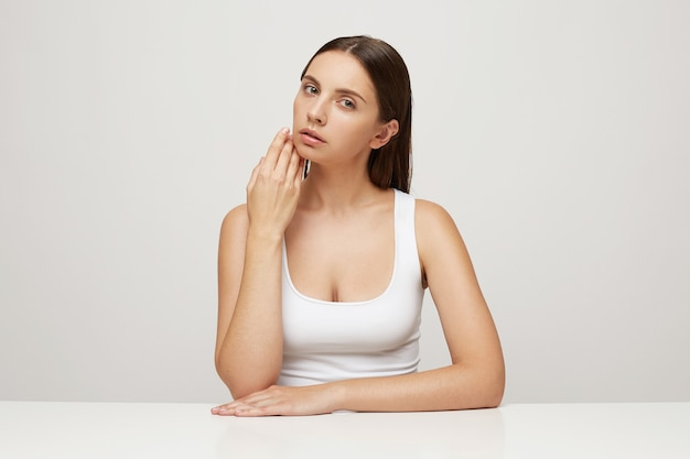完璧な健康的な新鮮な肌を持つ美しい女性がテーブルに座っています。