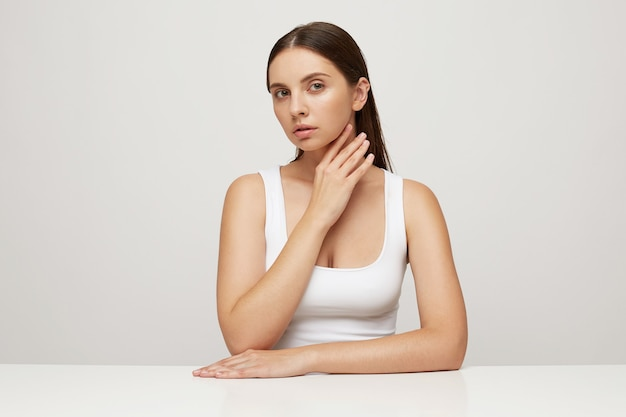 완벽 한 건강 한 신선한 피부를 가진 아름 다운 여자는 테이블에 앉아