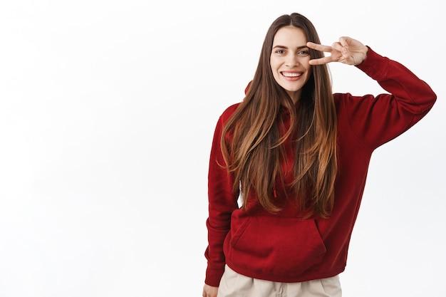 완벽한 건강한 미소와 자연스러운 긴 머리를 가진 아름다운 여성, 흔들리는 가닥, 평화의 v-sign을 보여주고 앞에서 행복해 보이는, 흰 벽 위에 서 있는
