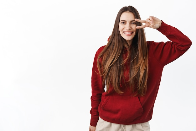 Beautiful woman with perfect healthy smile and natural long hair flying, strands waving, showing peace v-sign and looking happy at front, standing over white wall