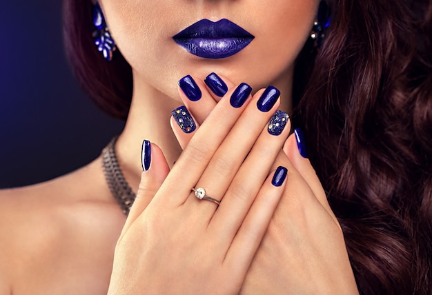 Beautiful woman with perfect make-up and blue manicure wearing jewellery.