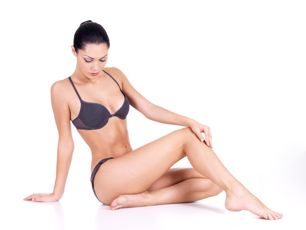 Bella donna con perfetto corpo sottile si siede su sfondo bianco